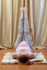 Беременная женщина делает дома гимнастику