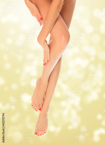 Perfect female legs on golden blurred background.
