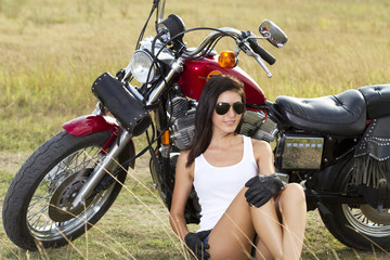 Young beautiful girl standing near a motorcycle