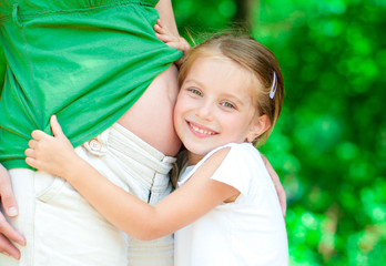 girl hugging mother's belly