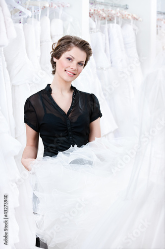 Shop assistant try to select a proper dress for the client