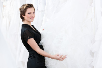 Shop assistant  is looking for dress for the bride