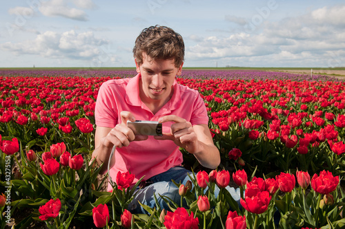 Yong man with  photo camera in field with tulips