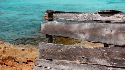 grunge gray wood on turquoise beach of Formentera island
