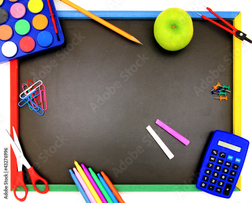 Blank blackboard with various colorful school supplies