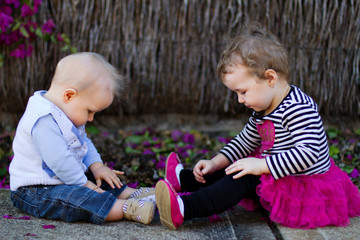 Baby boy and toddler girl sitting and playing outdoors
