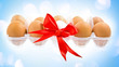 White egg wrapped around with red ribbon and pack