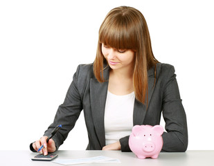 Young woman with a piggy bank and using
