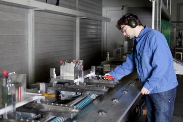 Ingenieur an einer Maschine in der Fabrikhalle