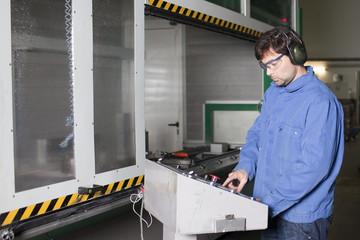 Ingenieur an Schaltern einer Maschine in der Fabrikhalle