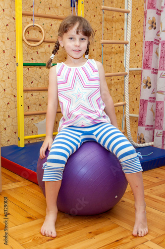Girl playing sports and sitting on the fitball