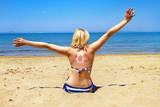 sun suncream on back of young woman on beach