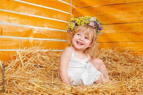 Beautiful little girl wearing a wreath sitting on the hay