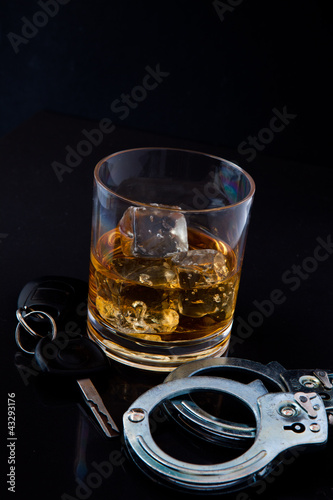 Whiskey on the rocks with car key and handcuff