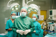 Surgeon joining his hand with two interns behind him