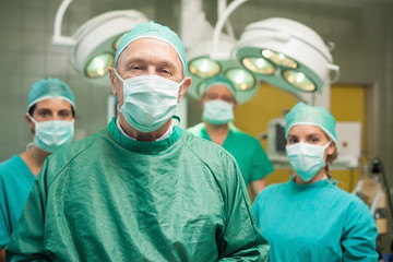 Smiling surgeon posing with a team