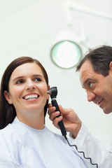 Doctor using an otoscope to look at the ear of a patient