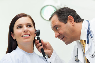 Doctor using an otoscope to look at the ear of his patient