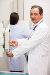 Doctor checking a machine while a patient is having a mammograph