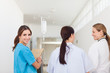 Nurse smiling while standing in a hallway with a patient and a d