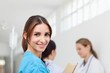Smiling woman  while standing in a hallway with a patient and a