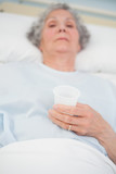 Elderly patient holding a plastic glass in her hand