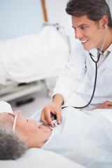 Doctor smiling while auscultating a patient