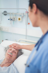 Patient lying on a bed closes her eyes