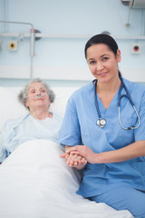 Nurse sitting on the bed next to a patient