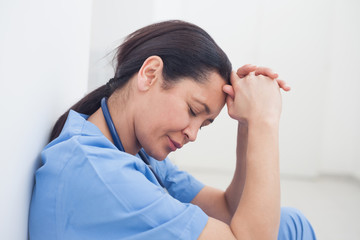 Upset nurse sitting on the floor