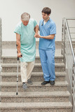 Male nurse assisting a patient on stairs