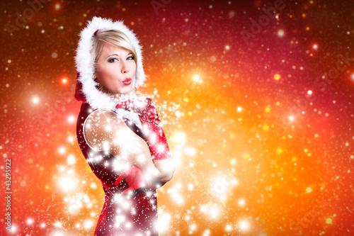 blonde Weihnachtsfrau pustet Schnee