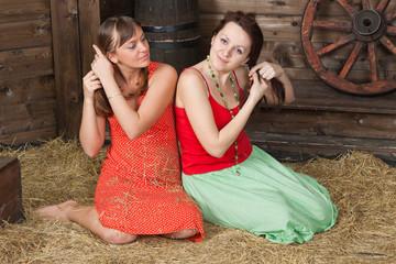 Young girls rest on a hayloft braiding hair