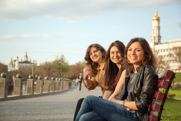 Girls sitting on a bench in city park