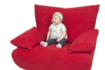 Baby girl seated in a big red sofa