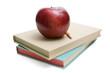 Apple on school books isolated on white