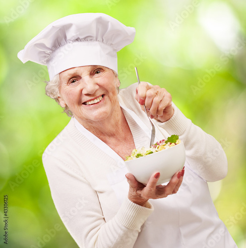 portrait of adorable senior cook woman eating salad against a na