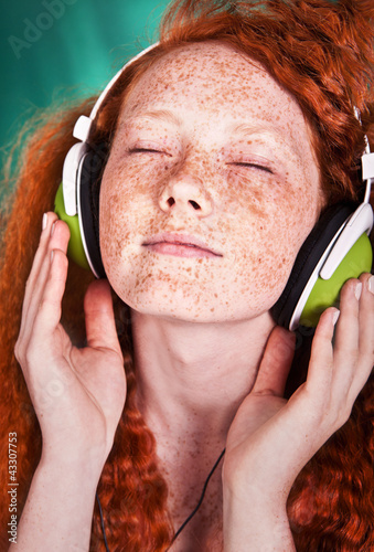 portrait of a young girl listening to music with headphones