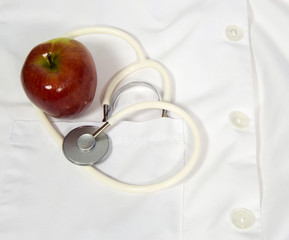 apple and stethoscope on a lab coat