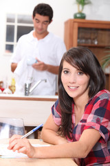 Woman doing paperwork while her boyfriend washes the dishes