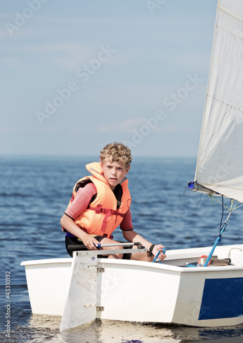 The boy operates the yacht