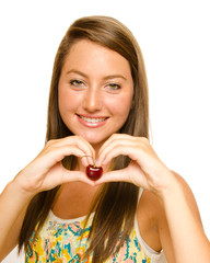 Smiling teenager making heart shape while holding cherry