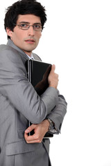 Businessman clutching his laptop