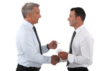 duo of businessmen exchanging visit cards