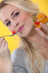 Blond woman eating fruit  salad