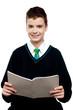 Charming schoolboy holding workbook