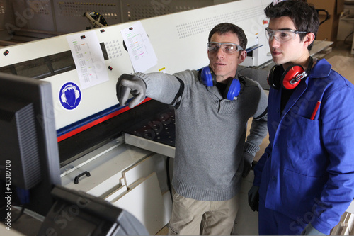 Two men operating factory machine
