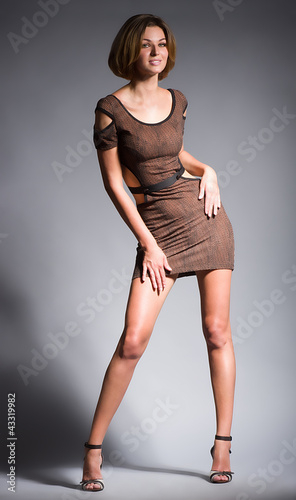 Sexy young woman in fashion dress on dark background.