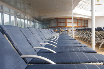 LIne of Blue Chaise Lounges on Deck of Ship