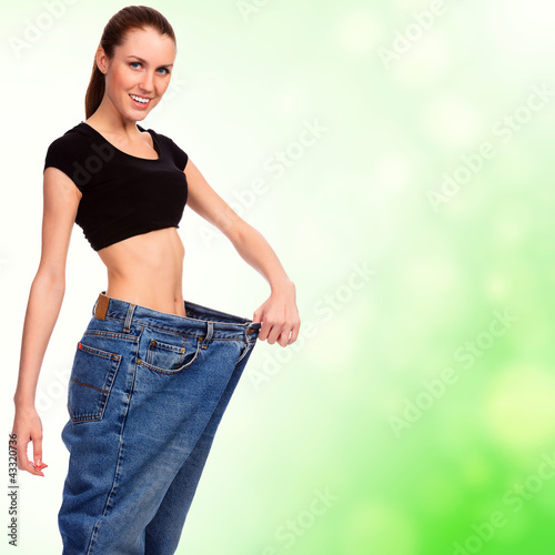 attractive young woman shows her old huge pair of jeans